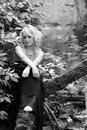 A moment of melancholy photo in black and white gracious and delicate blonde woman in long black dress sitting pensively on tree Royalty Free Stock Images