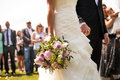 Moment in wedding bride and bridegroom holding hands with bouquet and guests background Royalty Free Stock Photography