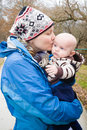 Mommy baby day a mother holding her young son kissing him on the cheek outside wearing warm clothes on a cold enjoying the fresh Royalty Free Stock Photography