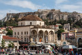 The monastiraki square with its tourists the former convent now folks museum with its arches and the massive acropolis with the Royalty Free Stock Photo