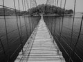 Monchrome rope bridge direct to lonely island across the lake in Stock Photos