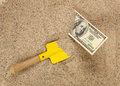 Money american hunderd dollar bills in sand and yellow shovel horizontal Stock Photos