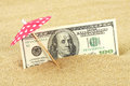 Money american hundred dollar bills in the beach sand under red and white dots sunshade Royalty Free Stock Photo