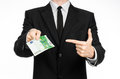 Money and business theme a man in a black suit holding a bill of euros and shows a hand gesture on an isolated white backgrou Royalty Free Stock Photos