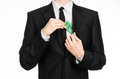 Money and business theme a man in a black suit holding a bill of euros and shows a hand gesture on an isolated white backgrou Stock Photography