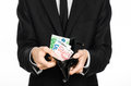 Money and business theme: a man in a black suit holding a purse with paper money Euro isolated on white background in studio Royalty Free Stock Photo