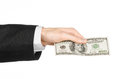 Money and business topic: hand in a black suit holding a banknote of 100 dollars on white isolated background in studio Royalty Free Stock Photo