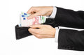 Money and business topic: hand in a black suit holding a wallet with banknotes 10,20 and 100 euro on white isolated background in Royalty Free Stock Photo