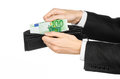Money and business topic: hand in a black suit holding a wallet with 100 euro banknotes isolated on white background in studio Royalty Free Stock Photo