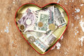 Money donation and saving in heart box Royalty Free Stock Photo