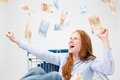 Money falling over a happy woman young sitting in shopping cart and cheering at lot of paper from above Stock Photography