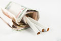 Money and group of cigarettes on white Royalty Free Stock Image
