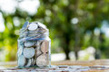 Money jar filled with coins on green bokeh