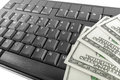 Money and keyboard laying on the computer Stock Photo
