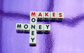 Money makes money text in uppercase letters on white cubes arranged crossword style with common letters m and n purple background Royalty Free Stock Photos