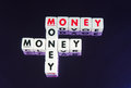 Money money money text inscribed in upper case letters on small cubes and arranged crossword style with common letters m and n Stock Photo