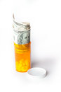 Money and Prescription Drugs in a container with a hundred dollar bill Royalty Free Stock Photo