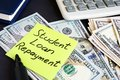 Money for Student Loan Repayment on a table. Royalty Free Stock Photo