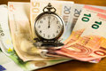 Money time is concept with euros and a pocket watch Royalty Free Stock Photo