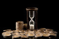 Money and time euro coins hourglass on black background studio shot Royalty Free Stock Photo