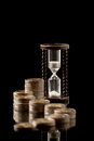 Money and time euro coins hourglass on black background studio shot Royalty Free Stock Photography