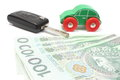 Money, wooden green toy car and key vehicle. White background Royalty Free Stock Photo