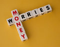 Money worries text and inscribed on small white cubes and arranged crossword style with common letter o yellow background Stock Photography