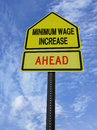 Monimum wage increase ahead conceptual sign with words minimum over blue sky Royalty Free Stock Photo