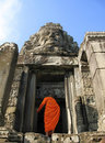 A monk enters Bayon Temple at Angkor Thom, Cambodia Royalty Free Stock Photo