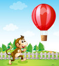 A monkey running outside the fence with a hot air balloon illustration of Royalty Free Stock Photo