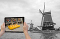 Monochromatic concept travel to netherlands in the bottom left of the photo are hands holding tablet whose screen contains color Stock Photo
