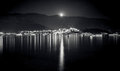 Monochrome landscape of full moon shining over mountains, city a Royalty Free Stock Photo