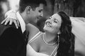 Monochrome portrait of bride and groom embracing and laughing closeup at windy day Stock Photo