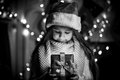 Monochrome portrait of smiling girl opening Christmas present bo Royalty Free Stock Photo