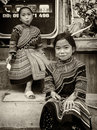 Monochrome - 2 Young minority tribe girls sit outside of mobile phone shop. Royalty Free Stock Photo