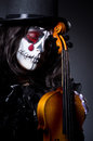 Monster playing violin in dark room Stock Photography
