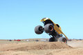 Monster truck yellow jumping over sand dune jump at public arena Royalty Free Stock Image
