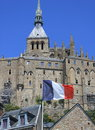 Mont st michel in normandy with the french flag in the foreground Royalty Free Stock Photo