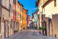 Montepulciano, Italy - August 25, 2013: Old narrow street in the center of town with colorful facades. Royalty Free Stock Photo