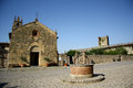 Monteriggioni tuscany italy piazza roma in with the old well the xiii century church of saint maria and the medieval city walls in Stock Photos
