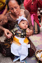 A 3-month-old Balinese-Hindu baby boy is dressed by his family in Hindu religious clothing during his baby-naming ceremony in Bali Royalty Free Stock Photo