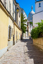 Montmartre in summer rue saint rustique paris france the street of with basilique du sacre coeur at the background Stock Photo