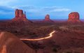 Monument valley the mittens and merrick butte after sunset with tourists cars coming back from the scenic driver a mile unpaved Royalty Free Stock Image