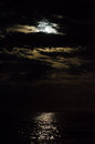 Moon covered with clouds by at the black sea Stock Photography