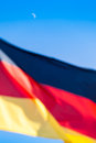 Moon over germany the at the blue sky and the colors of a german flag at the foreground Royalty Free Stock Photo