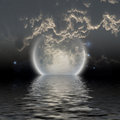Moon over water with low clouds Royalty Free Stock Photography