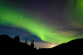 Moon rise hills northern lights aurora borealis intense bands of or or polar dancing on night sky over with light glowing from Royalty Free Stock Photos