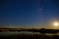 The moon and the stars in the night sky reflected in the river. Royalty Free Stock Photo