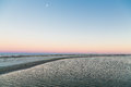 Moon at sunset over tidewater a shallow tidal pool or sunrise Stock Image