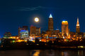 Moonrise over cleveland brightly lit ohio under a just risen full moon Royalty Free Stock Photos